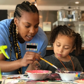 One of our volunteers engaging with a kiddo at the paint station.